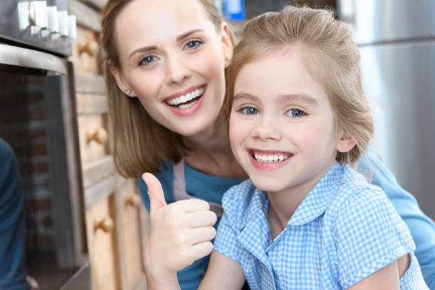 portrait of happy mother with daughter showing thumb up
